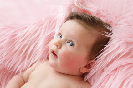 Newborn baby girl posed in a bowl on her back on blanket of fur